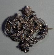 Broche en or jaune 18K (750/°°) et argent (800/°°) à décor de volutes serties de...